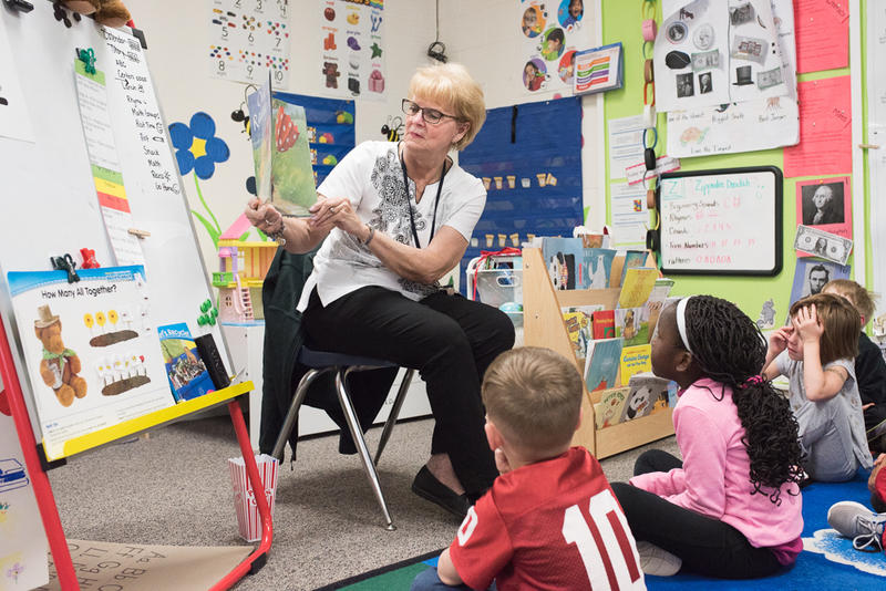 Nancy Novosad, a pre-K teacher's aide at Ranchwood Elementary in Yukon, reads to students on April 26.