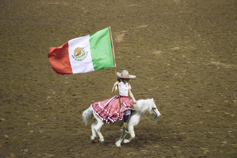 A girl carries a Mexican flag around the Jim Norick Arena.  The riders at the Cowboys of Color Rodeo were predominantly African-American, but Latino and Native American riders were featured as well.