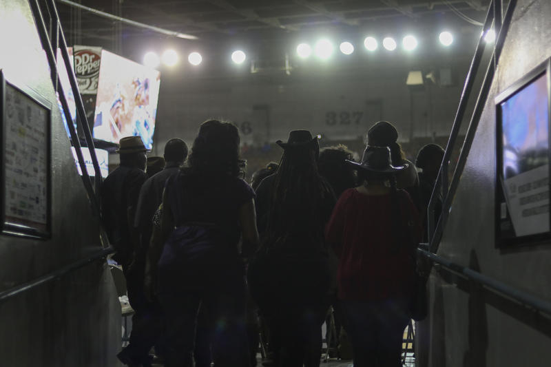 Spectators at the Cowboys of Color Rodeo watch the action before taking their seats in the stands.