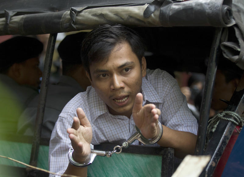Imprisoned Reuters journalist Kyaw Soe Oo speaks from a police truck as he leaves a court after his trial Wednesday, May 2, 2018, Yangon, Myanmar.