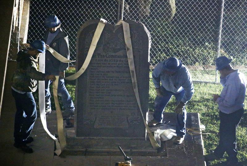 Workers remove the Ten Commandments monument from its base on the grounds of the state Capitol in Oklahoma City on Oct. 5, 2015, after the Oklahoma Supreme Court ruled the display violated the state constitution.