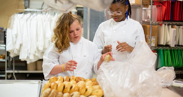 Students Faith Thomas, left, and A'Riyah Stepeny prepare bagels to give to students as part of a free breakfast program at Oklahoma Centennial Mid-High School in Oklahoma City Tuesday.