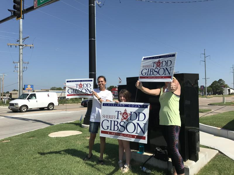 Supporters hold signs for Cleveland County sheriff candidate Todd Gibson.
