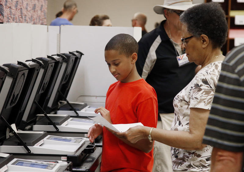 Arvelene Farmer, right, hands her grandson Jaylan Farmer, left, her ballot, so that he can place it into the voting machine, at the Oklahoma County Board of Elections, Thursday, June 21, 2018, in Oklahoma City.