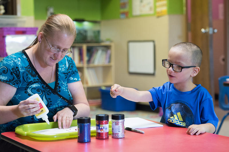 Master teacher Carolyn Wood applies glue to an art project with student Brendan Compton, 4, at Children's Discovery Center in Norman on July 24. The childcare facility, which takes children up to 5 years old, is currently full with a waitlist of families.