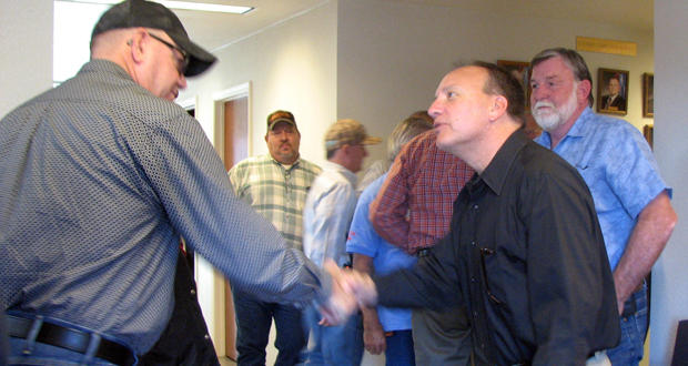 Former Talihina Veterans Center Director Roy Griffith, left, shakes hands with Choctaw Nation Chief Gary Batton at a fall 2017 open house of the veterans nursing home. Former Mayor Don Faulkner watches at right.