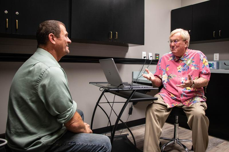 Dr. William Yarborough, right, speaks with patient Richard Potts at the Oklahoma Pain and Wellness Center in Tulsa.