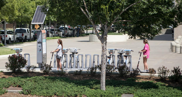 Two women ride Bird electric scooters past a Spokies bike-share station near Reno Avenue and Ron Norick Boulevard in Oklahoma City Friday.
