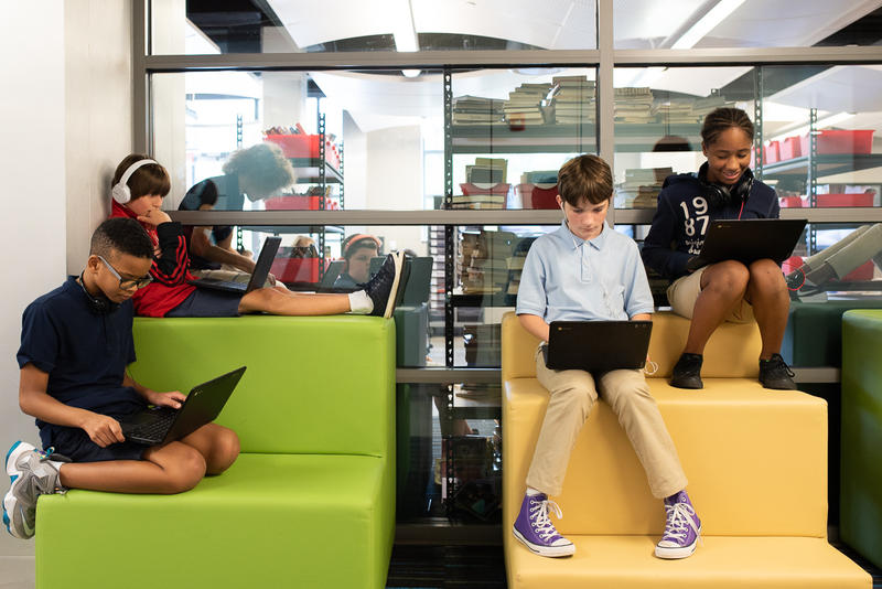 Students at John Rex Charter Middle School in Oklahoma City – sixth graders Finley Cunningham, top left, Direon Kelley, bottom left, Charlie Marshall and Taylor Ellis – sit on cushions in the hallway during a break from schoolwork.