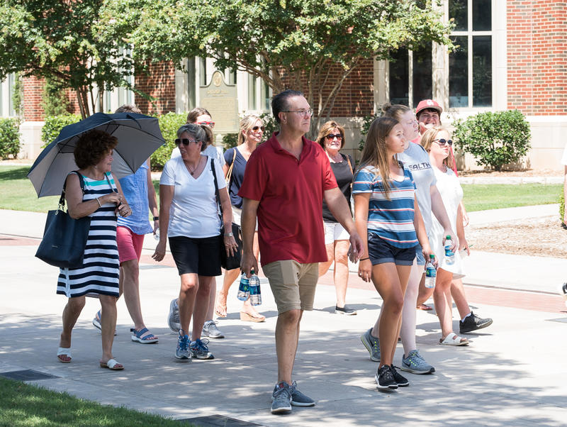 A student-led tour group walks on the south oval of the University of Oklahoma campus.