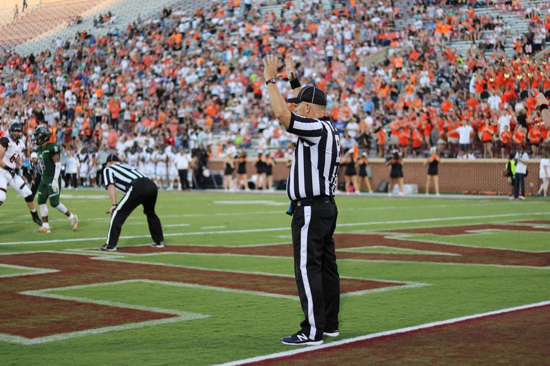 A back judge and a referee officiate a high school football game in Norman, August 2018.