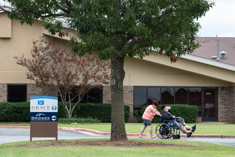 Kay Stokes pushes her husband, Roger, in a wheelchair outside of Grace Living Center in Oklahoma City. Grace is one of the nursing homes of which the City of Pauls Valley has become its designated owner.