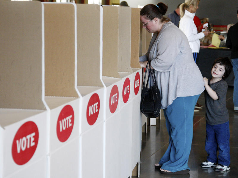 Thomas Benedetti, right, 3, holds onto his mother, Amy Benedetti, left, as she votes in Edmond, Okla., Tuesday, March 6, 2012.