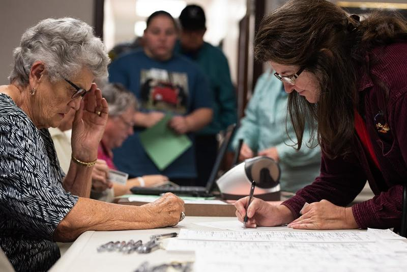 May Morgan signs her name in front of a volunteer before receiving a ballot at the Grady County Election Board in Chickasha on Friday, the second day of early voting.