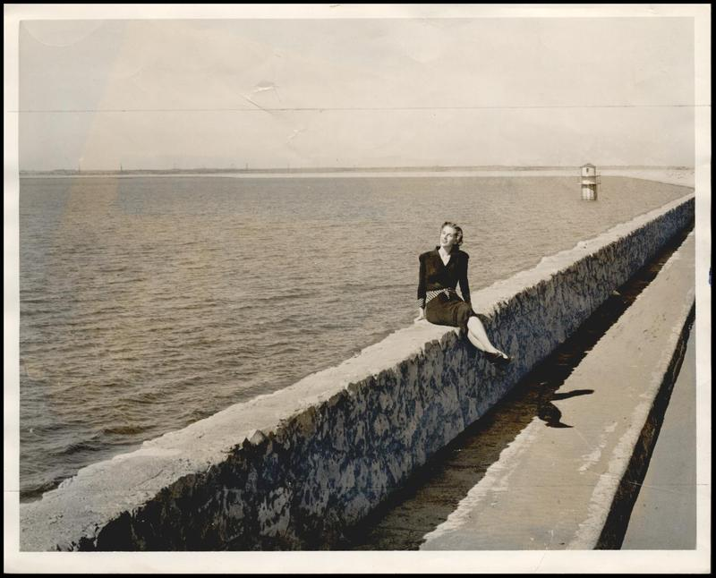 Reporter Maxine Cline sits on the stone wall atop the Bluff Creek Reservoir Dam in 1945.