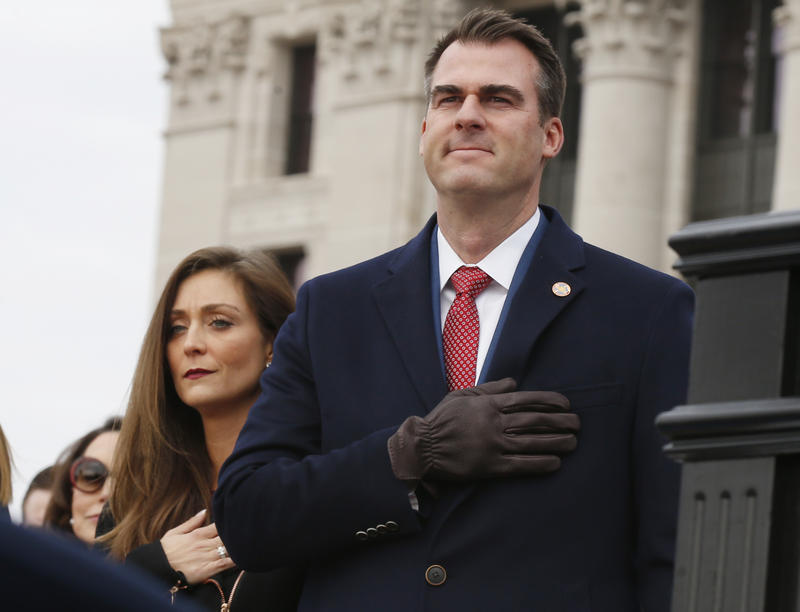 Oklahoma Governor Kevin Stitt, right, stands with his wife Sarah Stitt, left, as they hold their hands over their hearts for the playing of the national anthem during inauguration ceremonies in Oklahoma City, Monday, Jan. 14, 2019.