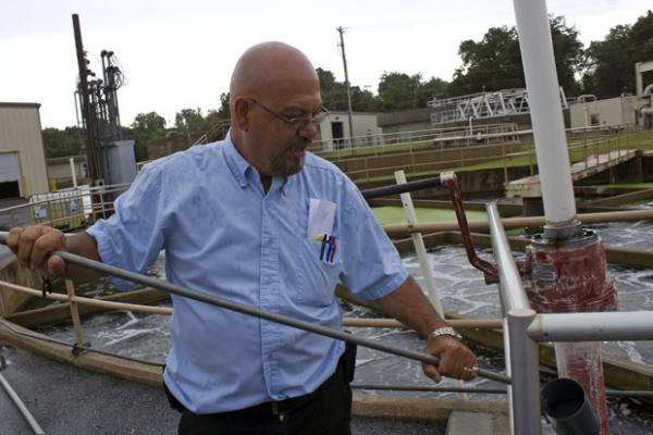 Tom Myers, superintendent of the new wastewater treatment plant in Siloam Springs, Ark., holds a sample of treated water that will flow into Oklahoma's Flint Creek.