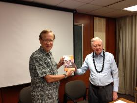 "Dr. Charles Morrison (left), president of the East West Center, holds up a copy of ""Steps to Paradise and Beyond,"" written by Dr. Verner Bickley, the first director of the Culture Learning Institute, 1972-1981.  Bickley returned to the Center to meet with former colleagues and talk about his book."