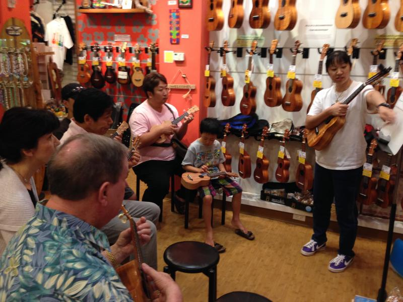Gina Sunada teaches ukulele in Waikiki to a class of six people.