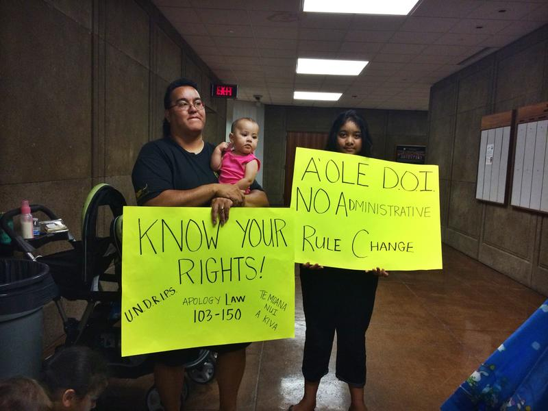 A family holds signs protesting federal recognition in the State Capitol lobby.