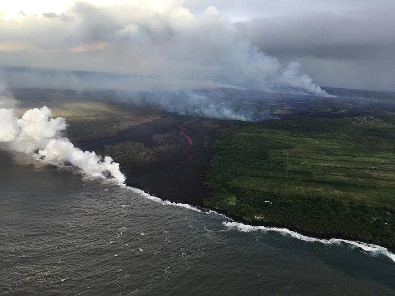 The fissure complex, pictured in the upper right, continues to feed a meandering lava flow (in the center). Lava in the easternmost lobe is entering the ocean (white plume).