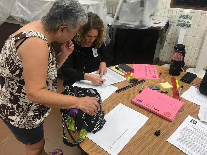 A County Civil Defense official helps a resident obtain a permit. The agency created a permit system for residents to streamline the re-entry/retrieval process.