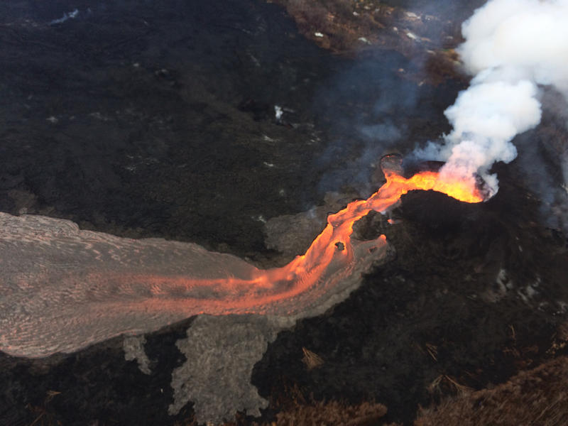 Aerial view of lava fountain at Fissure 8 and uppermost lava channel during an early morning overflight of the lava flow field.