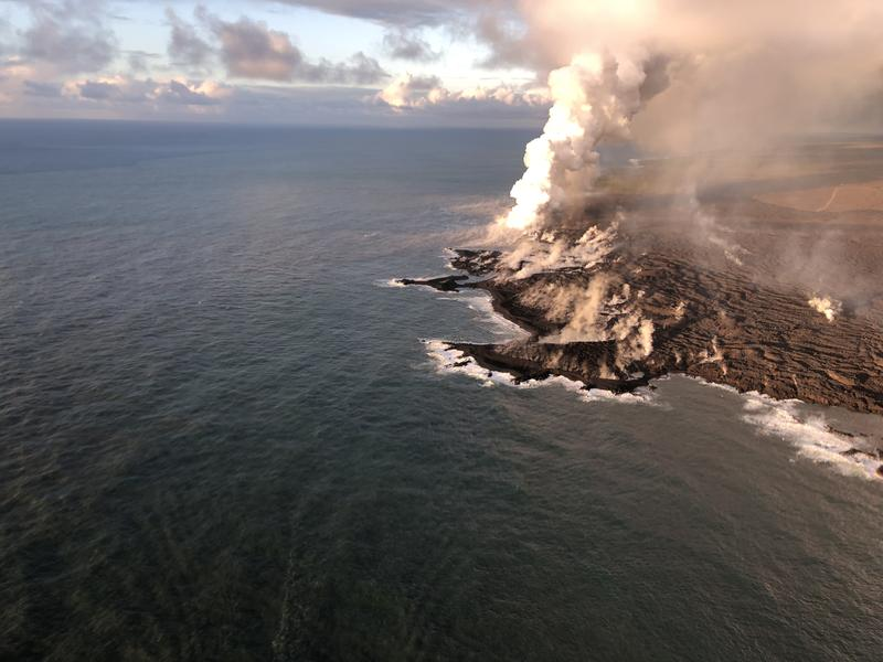 View of the ocean entry and the resulting laze plume where lava is entering the sea. As of June 12, lava entering the ocean had added about 100 ha (250 acres) of new land to the Island of Hawai'i.