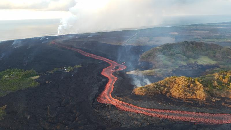 Fissure 8 lava flows in an open channel all the way to the ocean. Kapoho Crater is the vegetated hill on the right side of the photograph. Ocean entry plume seen in the distance.