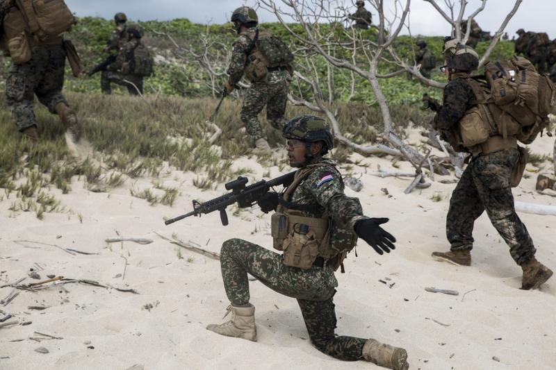 Malaysian and U.S. Marines push toward an objective on Pyramid Rock Beach during an amphibious landing demonstration.