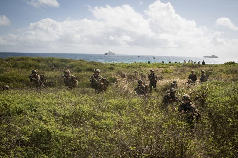U.S. Marines move inland from Pyramid Rock Beach. HMAS Adelaide assault ship in the background.