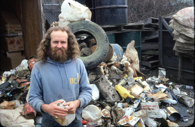 Greg Abbott in front of a wall of trash from early beach clean ups in 1977.