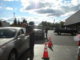 Members of Oregonians for Immigration Reform collect ballot signatures at a Milwaukie parking lot.