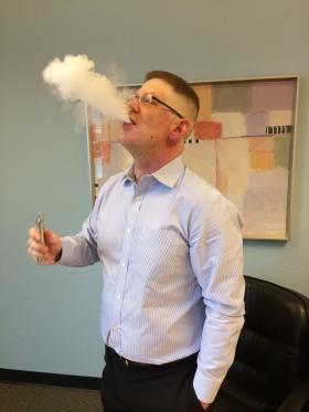 Justin Newman exhales vapor from an e-cigarette.