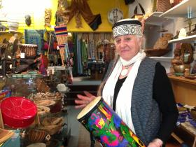 Joanie Kleban bangs on a conga drum in her store, Greater Goods.