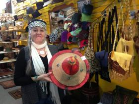 Joanie Kleban shows off one of her many hats at Greater Goods.