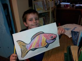 Siuslaw Elementary student shows off his salmon art.