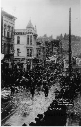 "An image from a cellulose nitrate negative at the Land County Historical Society.  ""Veterans of the 65th Regiment returning to Eugene after World War I. View looking north on Willamette Street, Eugene, Skinner Butte in background."""
