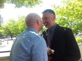 Eric Gates and Jose Soto lean in for a kiss during their marriage ceremony outside the Lane County Building in Eugene.
