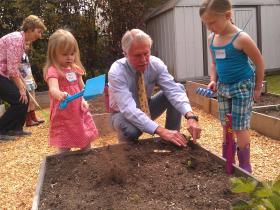 Governor Kitzhaber helps children in the garden at Friendship Preschool in Eugene.