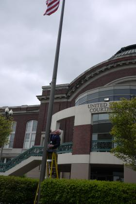 Patrick Daly lowers the flag to half-mast outside the federal courthouse at Tacoma's Union Station.