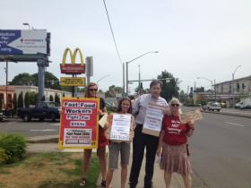 Lauren Regan (far left) and Leonard Stoehr (center) join other activists protesting low wages for fast food workers.