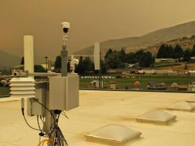 A portable, temporary air monitor was placed on the roof of the high school in Entiat and has been collecting samples since Thursday. Note the ground-hugging wildfire smoke in background.