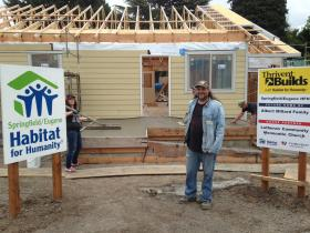 Albert Millard stands in front of his home as Habitat for Humanity volunteers work on the siding and the cement ramp in the front.