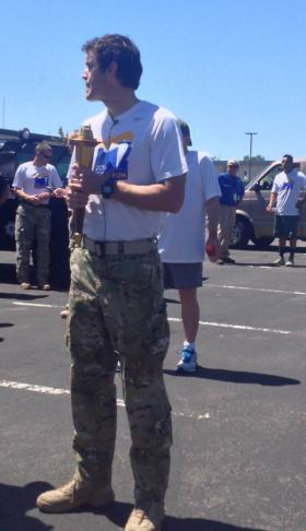 A police officer poses with the Flame Of Hope for the Special Olympics Torch Run