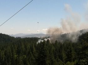 A helicopter drops water on a house fire off Fox Hollow Road in South Eugene.