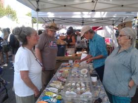 Farmers Market customers taste cheeses at the Ferns Edge Dairy booth.
