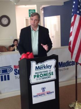 "U.S. Senator Jeff Merkley speaking at Sheldon Village. The boxing gloves were a gift from NCPSSM President Max Richtman to ""keep fighting"" for seniors."
