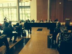 Panel members and audience listen to public comment at Ford Alumni Center on U of O campus.