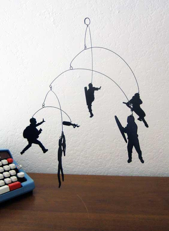 Andrea Leggitt's laser cut mobile designs include unusual subjects like riot cops and molotov cocktails.